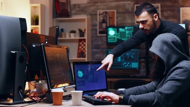 Eine gefährliche hackerin mit kapuze und ihr partner hacken die regierung und pflanzen eine malware.