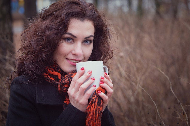 Eine gefrorene frau trinkt ihren heißen tee oder kaffee aus einer tasse.