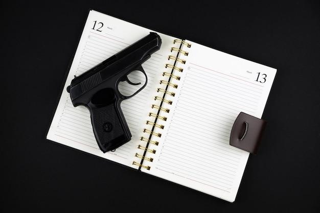 Eine geladene traumatische pistole liegt auf einem offenen notizbuch auf einer schwarzen oberfläche