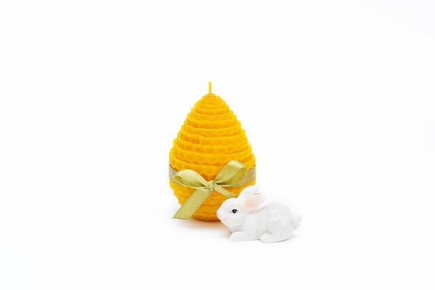 Eine gelbe dekorative natürliche bienenwachskerze mit einem honigaroma für den innenraum in form eines ostereies
