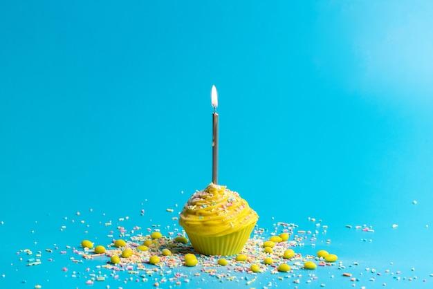 Eine gelbe geburtstagstorte der vorderansicht mit kerze auf blau