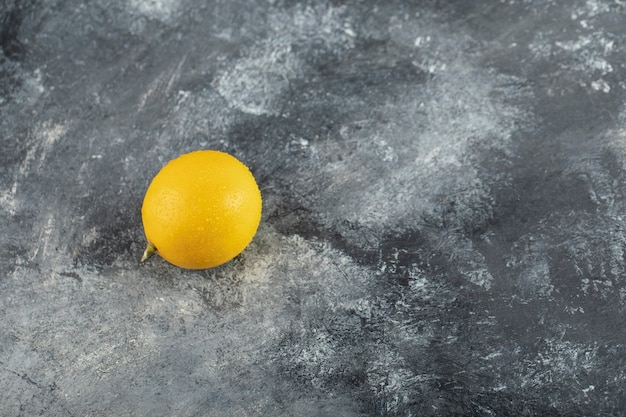 Eine gelbe reife zitrone auf einer marmoroberfläche.