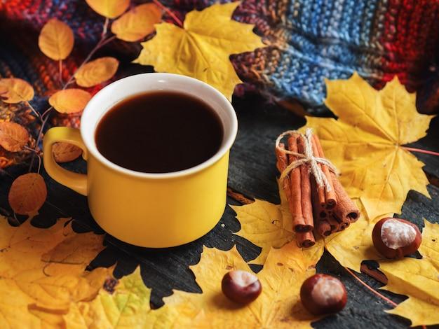 Eine gelbe tasse kaffee auf dem tisch mit gelbem herbstlaub und einem gestrickten schal