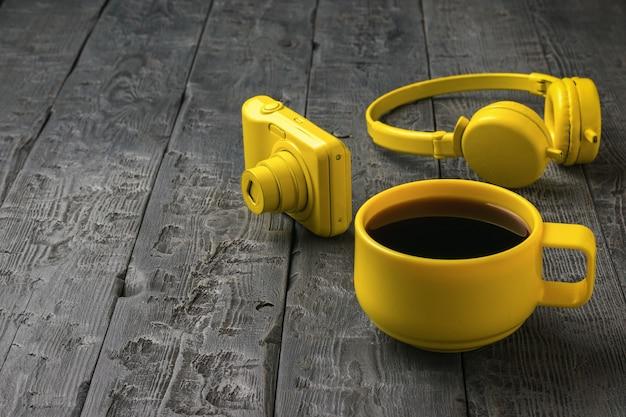 Eine gelbe tasse kaffee, kopfhörer und eine kamera auf einem holztisch. farben-trend. stilvolle accessoires.