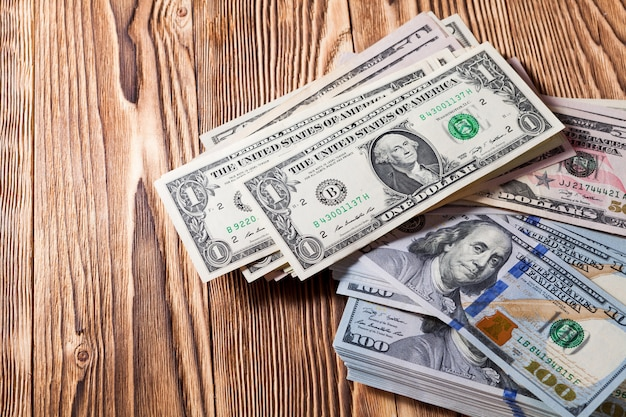 Eine geldbörse mit den amerikanischen dollars ist auf einem hölzernen hintergrund isoliert