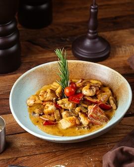 Eine gemüsesuppe der vorderansicht mit fleisch und tomate auf dem braunen tischmahlzeitnahrungsmittelfleischgemüse