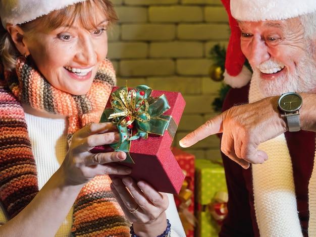 Eine geöffnete schachtel mit rotem weihnachtsgeschenk hält von unscharfen älteren kaukasischen paaren mit überraschtem glücklichem gesicht zusammen. weihnachts- und neujahrsfeier.