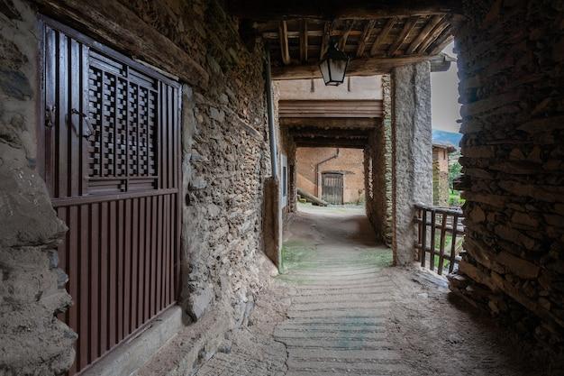 Eine gepflasterte straße, umgeben von lehm- und schieferhäusern, die einen alten und dunklen durchgang bilden