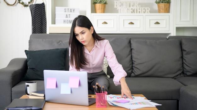 Eine geschäftsfrau arbeitet mit laptop-computer und analysiert geschäftswachstumsdiagrammdaten im wohnzimmer, arbeit von zu hause, geschäftstechnologiekonzept.
