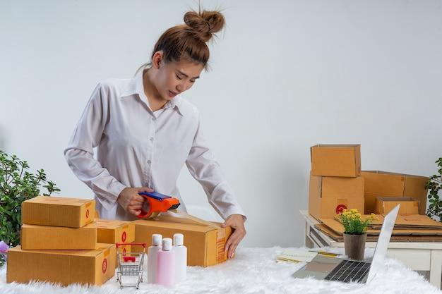 Eine geschäftsfrau arbeitet online und versucht, kunden zu hause büroverpackungen an der wand zu antworten.