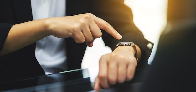 Eine geschäftsfrau, die auf eine armbanduhr während ihrer arbeitszeit zeigt, während sie auf jemanden im büro wartet