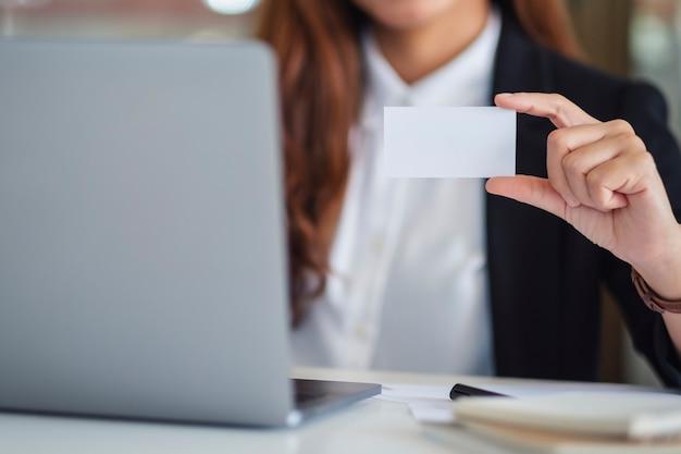 Eine geschäftsfrau, die eine leere visitenkarte hält und zeigt, während sie einen laptop im büro verwendet