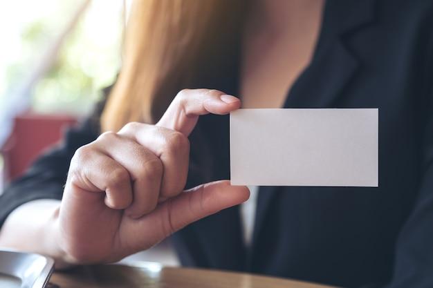 Eine geschäftsfrau, die eine leere visitenkarte hält und zeigt