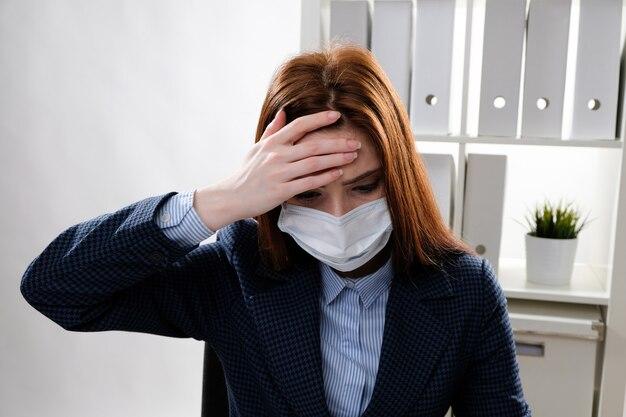 Eine geschäftsfrau, die in einer medizinischen maske arbeitet, fühlt sich krank