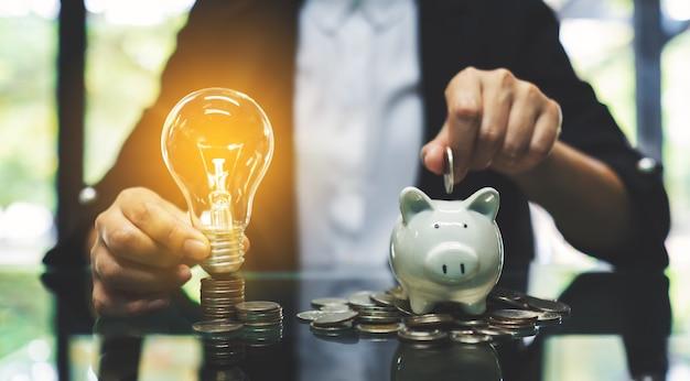 Eine geschäftsfrau, die münze in sparschwein und eine glühbirne über münzen stapelt, stapelt auf dem tisch, um geld und finanzielles konzept zu sparen