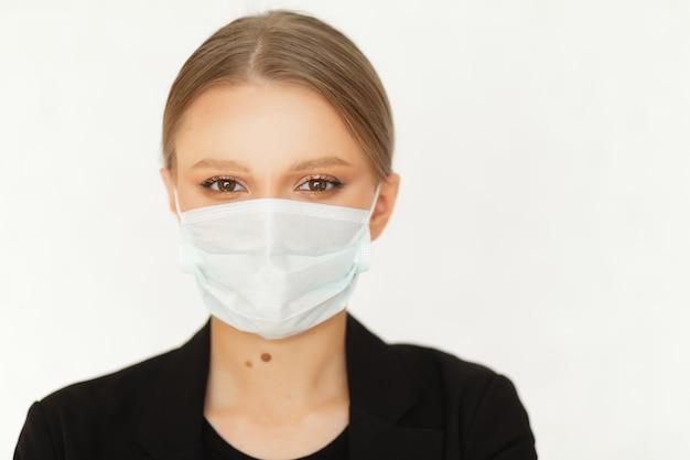 Eine geschäftsfrau im anzug hat eine maske zum schutz vor einem virus bei der arbeit aufgesetzt