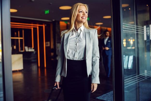 Eine geschäftsfrau in einem grauen blazer, einem weißen hemd und einem schwarzen rock trägt gepäck und verlässt das hotel. geschäftsreise, touristische ziele, bereit für ein offizielles treffen