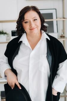 Eine geschäftsfrau in einem weißen hemd und einer hose steht mit einem hut in den händen im büro.