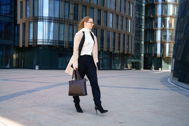 Eine geschäftsfrau in mantel und anzug, die eine tasche in der hand hält, geht tagsüber in die nähe des geschäftszentrums. konzeptionelles horizontales foto