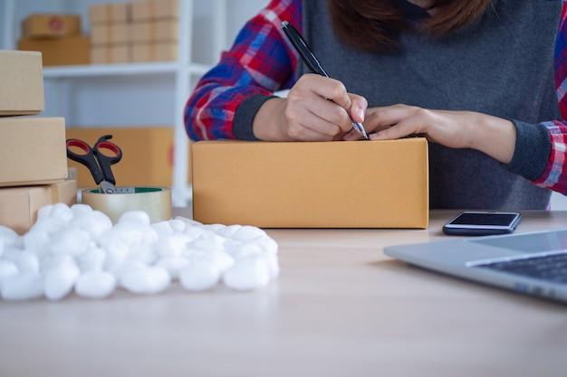 Eine geschäftsfrau schreibt ein kistengesicht und bereitet die kiste vor, um das produkt an online-käufer zu liefern. kleine unternehmen ideen für kleine und mittlere unternehmen
