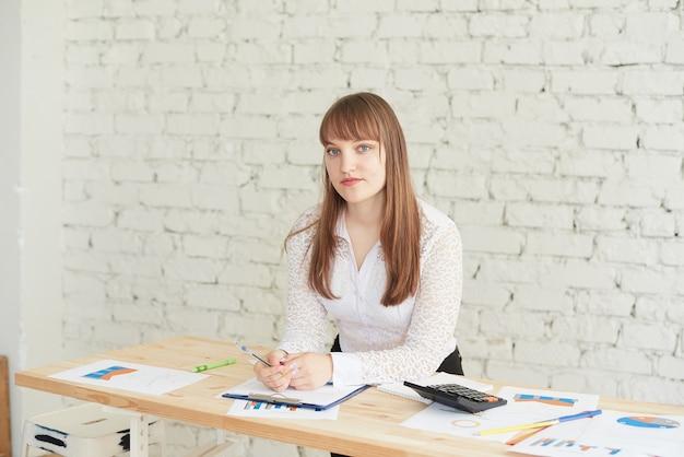 Eine geschäftsfrau steht mit geschäftsberichten an einem tisch und schaut in die kamera.