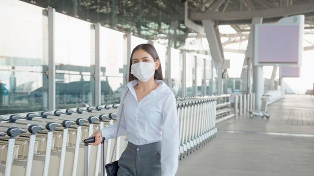 Eine geschäftsfrau trägt auf dem internationalen flughafen eine schutzmaske und reist unter der covid-19-pandemie