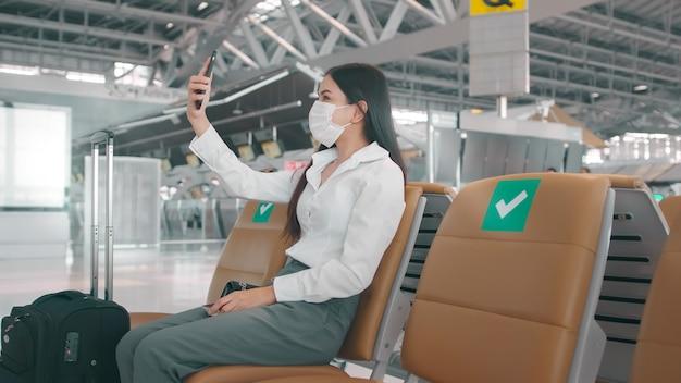 Eine geschäftsfrau trägt auf dem internationalen flughafen eine schutzmaske, videoanrufe zu ihrer familienreise unter covid-19-pandemie