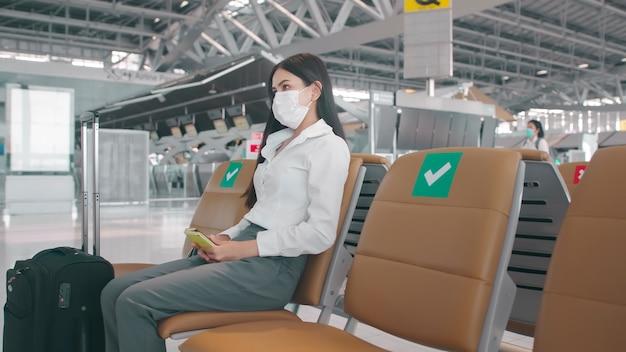 Eine geschäftsfrau trägt eine schutzmaske auf dem internationalen flughafen und reist unter der covid-19-pandemie
