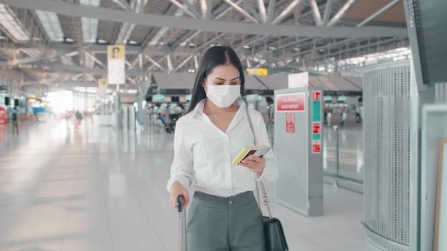 Eine geschäftsfrau trägt eine schutzmaske auf dem internationalen flughafen