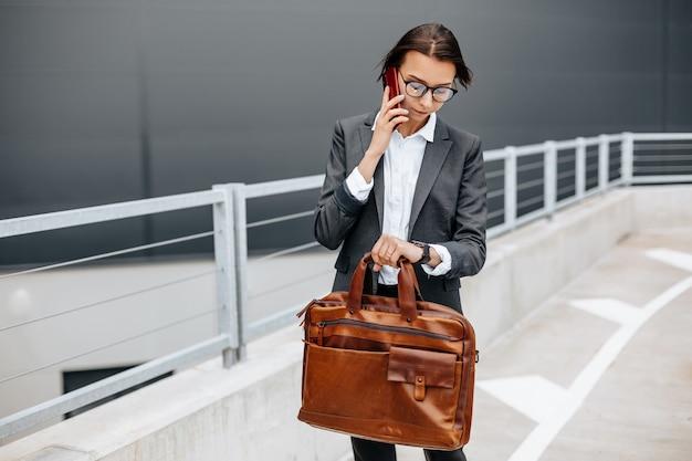 Eine geschäftsfrau überprüft die zeit in der stadt während eines arbeitstages und wartet auf ein treffen