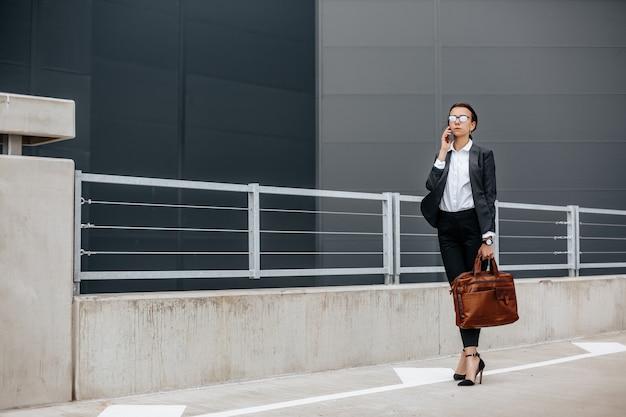 Eine geschäftsfrau überprüft während eines arbeitstages die zeit in der stadt und wartet auf ein treffen. disziplin und timing. ein mitarbeiter geht zu einem firmenmeeting.