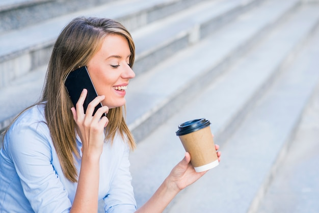 Eine geschäftsfrau überprüfung per e-mail über handy und hält eine kaffeetasse gegen städtische szene.