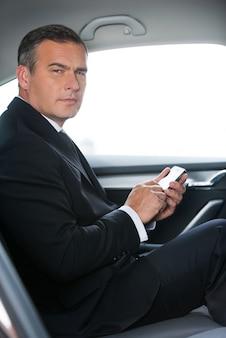 Eine geschäftsnachricht eingeben. seitenansicht eines selbstbewussten reifen geschäftsmannes, der eine nachricht auf seinem smartphone eingibt und auf die kamera schaut, während er auf dem rücksitz eines autos sitzt