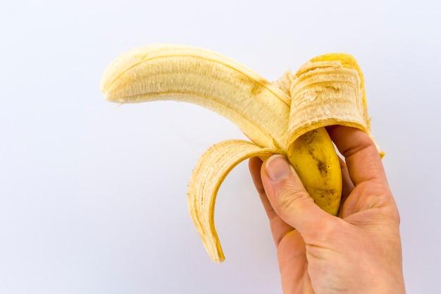 Eine geschälte banane in der hand einer frau auf weiß