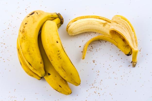Eine geschälte banane und ein bündel bananen auf weiß