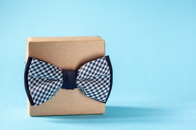 Eine geschenkbox in kraftpapier eingewickelt und mit der fliege auf blauem hintergrund gebunden. konzept vatertag.