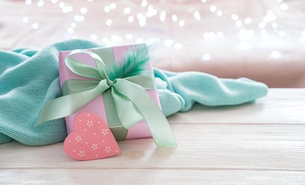 Eine geschenkbox und ein herz auf einem weichen hellen hintergrund mit einer leuchtenden girlande. seitenansicht mit platz zum kopieren. das konzept der urlaubshintergründe.