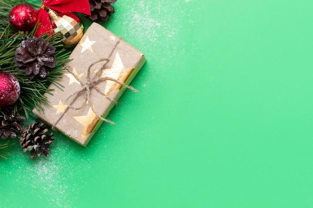 Eine geschenkbox und ein zweig eines weihnachtsbaums mit spielzeugbällen und zapfen auf grünem hintergrund