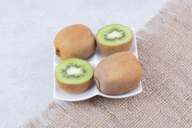 Eine geschnittene kiwi in weißem teller auf sackleinen