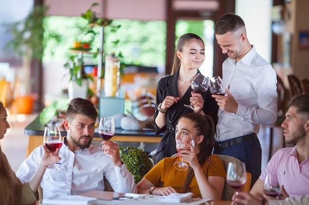 Eine gesellschaft von freunden feiert das treffen in einem restaurant.