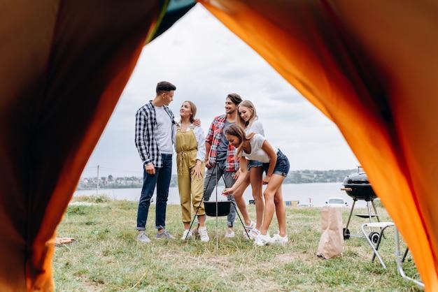Eine gesellschaft von freunden hat lustige zeit auf dem campingplatz