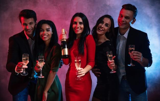 Eine gesellschaft von fünf jungen und attraktiven leuten feiert eine party, genießt gesellschaft, trinkt champagner und posiert zusammen mit flöten