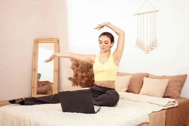Eine gesunde lebensweise. eine frau auf dem bett. online-morgenübung mit einem laptop.