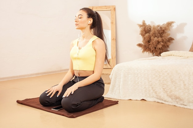 Eine gesunde lebensweise. eine frau macht sport und hört musik. auf einer fitnessmatte sitzen. yoga