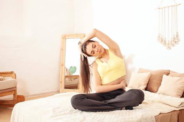 Eine gesunde lebensweise. eine frau macht yoga auf ihrem bett zu hause. morgenübung.