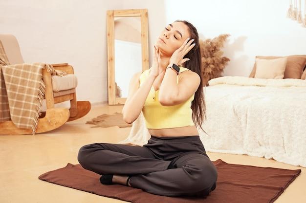 Eine gesunde lebensweise. eine frau macht yoga, sitzt in einer lotussitzung. matte, übung gesichtsmassage