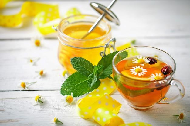 Eine gesunde tasse tee, ein glas honig und blumen. tiefenschärfe.