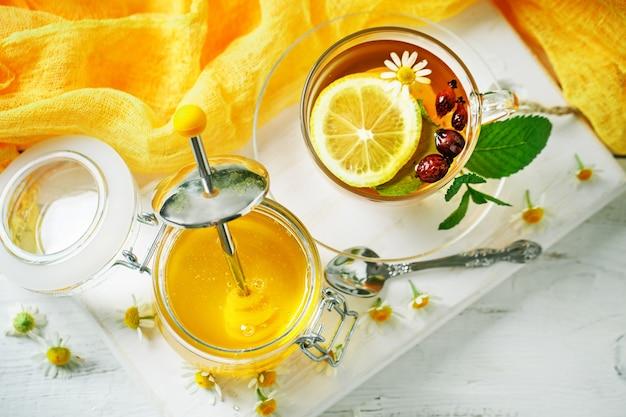 Eine gesunde tasse tee, ein glas honig und blumen.