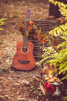 Eine gitarre steht in der nähe eines weidezauns, der mit herbstlaub umwickelt ist
