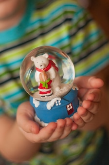 Eine glaskugel mit einem bären in den händen eines kindes